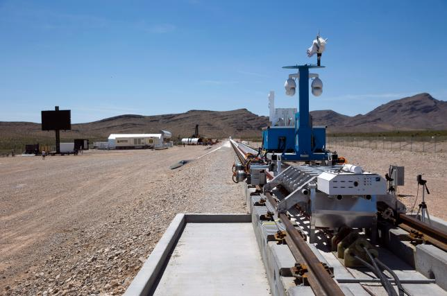 A silver-colored sled and recovery vehicle are displayed on a test track after a propulsion open-air test at Hyperloop One in North Las Vegas