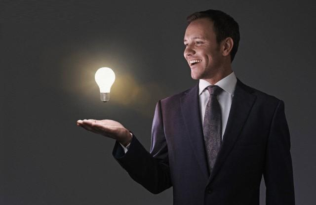 Portrait of mid adult man with illuminated light bulb